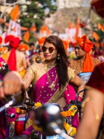 Mumbai, India - MARCH 18, 2018 : A beautiful indian female dressed in traditional attire driving a bike during a procession celebrating 'Gudhi Padwa' or the Maharashtrian new year in Mumbai
