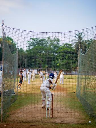 Mumbai, India - April 21, 2018: Unidentified boy practicing batting to improve cricketing skills at Mumbai grounds