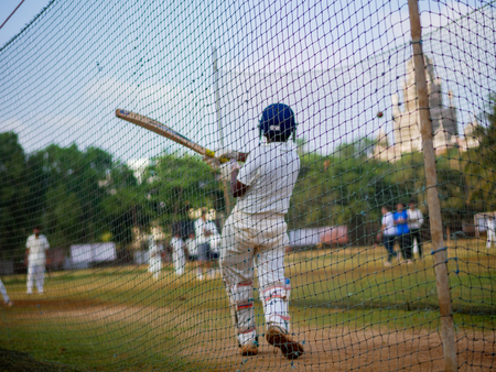 Mumbai, India - April 21, 2018: Unidentified boy practicing batting to improve cricketing skills at Mumbai grounds