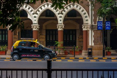 MUMBAI, INDIA - DECEMBER 12, 2014 : Famous Mumbai taxi carrying passengers on streets of Mumbai
