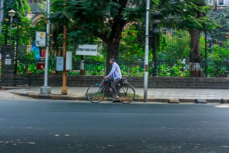 MUMBAI, INDIA - DECEMBER 4, 2016 : A man driving a bicycle on streets of Mumbai