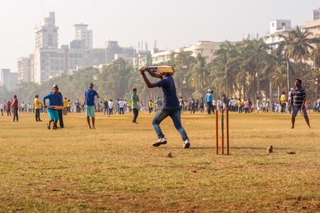 MUMBAI, INDIA - DECEMBER 4, 2016 : Young boys playing cricket with tennis ball at Mumbai grounds Editorial