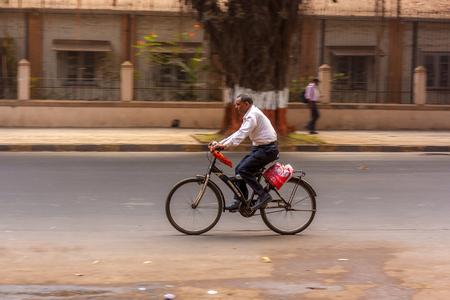 MUMBAI, INDIA - JANUARY 14, 2017 : A man driving a bicycle on streets of Mumbai