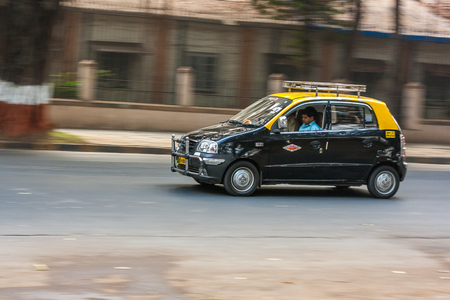 MUMBAI, INDIA - JANUARY 14, 2017 : A famous black & yellow collored taxi running on the streets of Mumbai Editorial