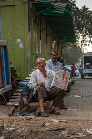 MUMBAI, INDIA - JANUARY 29, 2017 : An elderly men reading news paper at streets of Mumbai