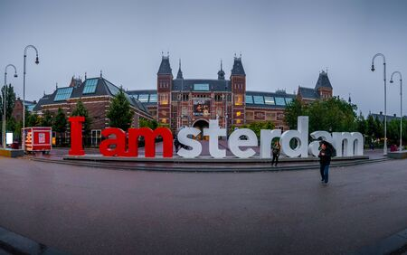 Amsterdam, Netherlands - August 26, 2018: Unidentified Tourist at the red and white I am Amsterdam sign in centre of amsterdam