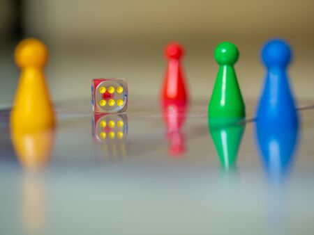 Reflection of Colorful plastic player pawn for boardgame and dice represent a major tool of game playing