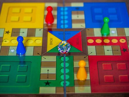 Pieces and a die on a Ludo board game 스톡 콘텐츠