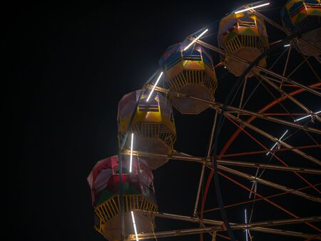 A colourful Giant wheel at amusement park illuminated at night in India