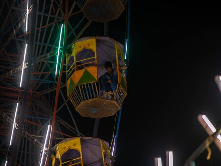 Mumbai, India - December 01, 2019: Unidentified kid watching from colourful Giant wheel at amusement park illuminated at night in India 스톡 콘텐츠
