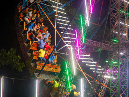 Mumbai, India - December 01, 2019: Indian family enjoying thrilling  ride at amusement park illuminated at night