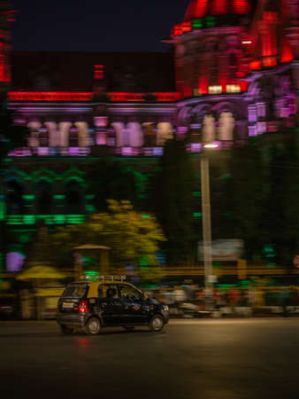 Mumbai, India - January 26, 2020 : Black and Yellow taxi runnig on the streets of south Mumbai near CST station