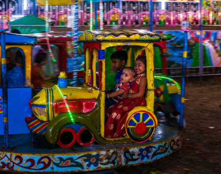 Mumbai, India - December 01, 2019: Indian kid enjoying carousel ride in a Train engine at amusement park