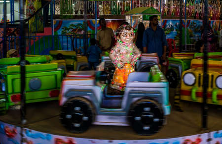 Mumbai, India - December 01, 2019: Indian kids enjoying carousel ride in a open car at amusement park 에디토리얼