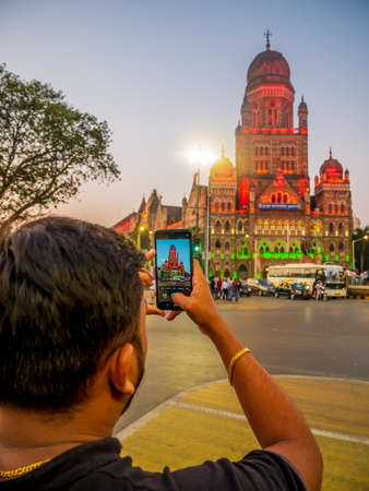 Mumbai, India - January 26, 2020 : Unidentified man clicking a selfie of illuminated BMC building in India flag color