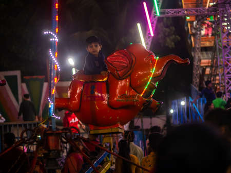 Mumbai, India - December 01, 2019: Indian kids enjoying carousel ride in elephant at amusement park 에디토리얼