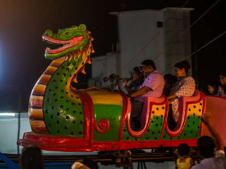 Mumbai, India - December 01, 2019: Indian family enjoying thrilling roller coaster ride at amusement park illuminated at night