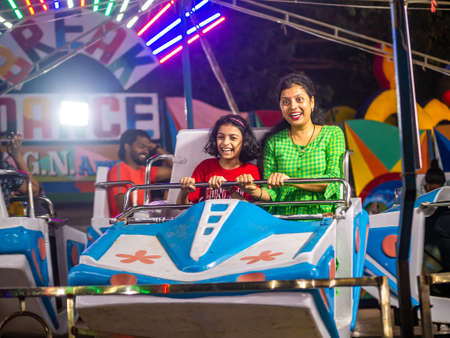 Mumbai, India - December 01, 2019: Indian family enjoying carousel ride  at amusement park 에디토리얼