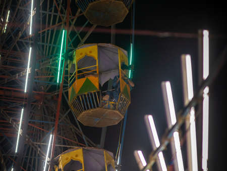 Mumbai, India - December 01, 2019: Unidentified kid waving from colourful Giant wheel at amusement park illuminated at night in India