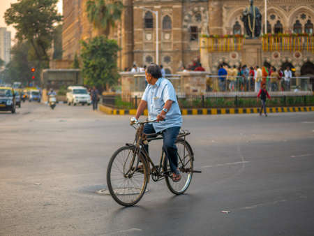 Mumbai, India - January 26, 2020 : An elderly man ridding a bicyle near CST station in South Mumbai