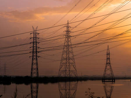 High-voltage power lines at Sunrise/sunset. electricity distribution station.Saltpans in Mumbai.
