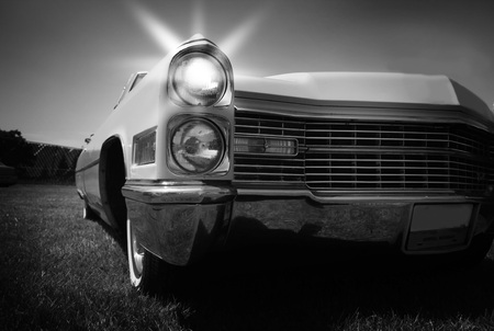 Glowing head lamp of a vintage car in monochrome photo