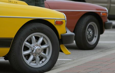 Two old sport cars parked in a parking lot photo