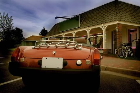 Classic sports car parked in front of a store photo