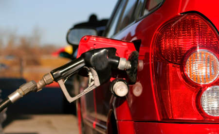 cropped photo showing a hose filling a car with gasoline or petrol. Stock Photo - 1544268