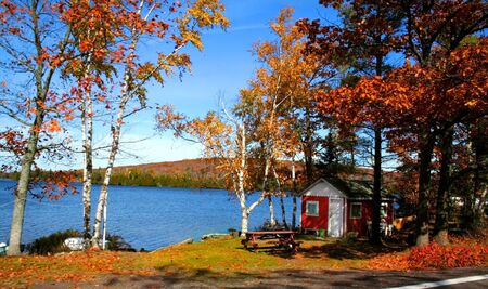 Small cabin by the lake during autumn time photo