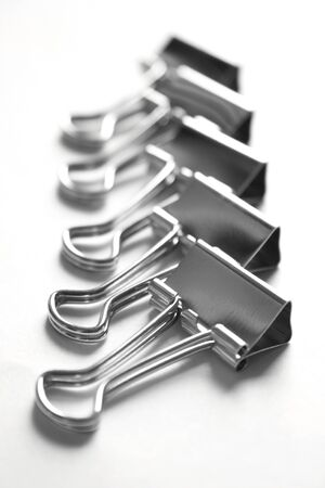 disorganize: Metalic paper clips in a row on a white background