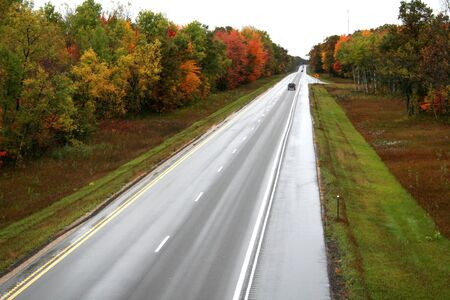tollway: highway and autumn scene on a rainy day Stock Photo