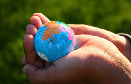 kid holding earth in his hand on green back ground photo