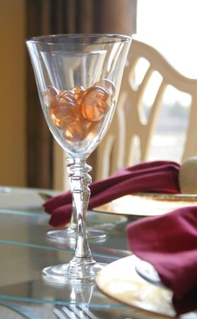 pebles: Wine glass with orange pebles on a dining table