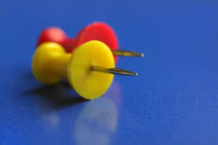 An abstract of red and yellow push pins on blue background