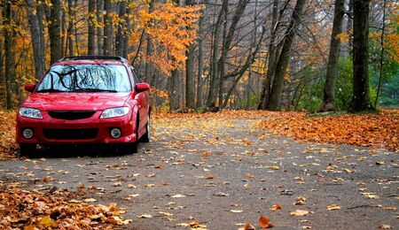 Red car parked in a park during autumn in michigan