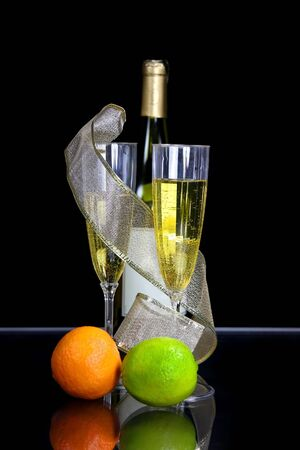 Two champagne glasses and bottle against black background  photo
