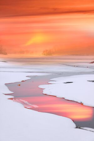 Strem flowing through frozen lake photo