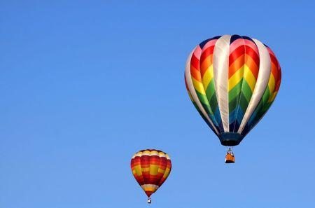 Twee kleurrijke hete lucht ballonnen in de blauwe hemel
