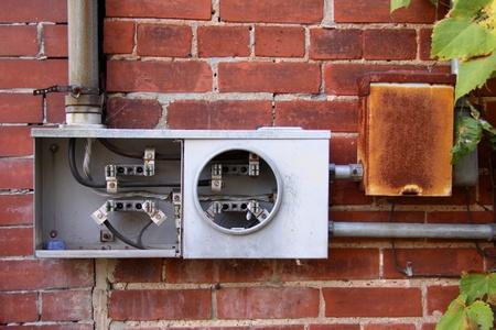 contador electrico: Medidor el�ctrico roto en una pared de ladrillo Foto de archivo