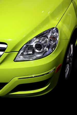 new motor vehicles: Close up shot of bright green modern car head lamp