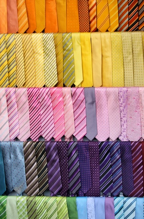 mens: colorful ties with different designs on wardrobe Stock Photo