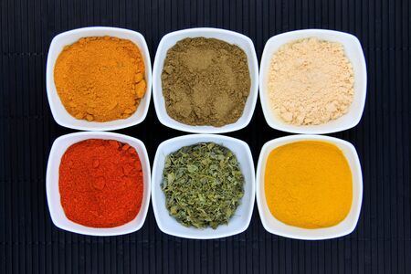 Different variety of spices  on black mat Stock Photo - 9141917