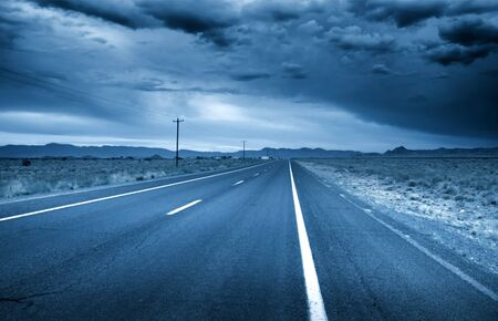 empty space: Desert drive with stormy sky in blue color Stock Photo