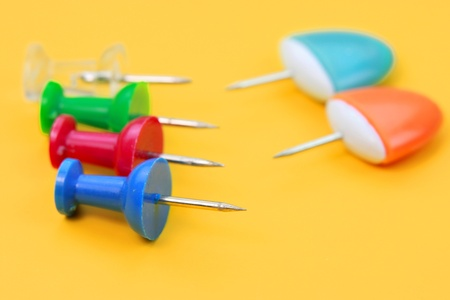 Colorful push pins on a yellow background photo