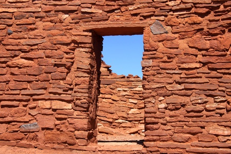 pueblo: Old mud wall and entrance build with red rocks