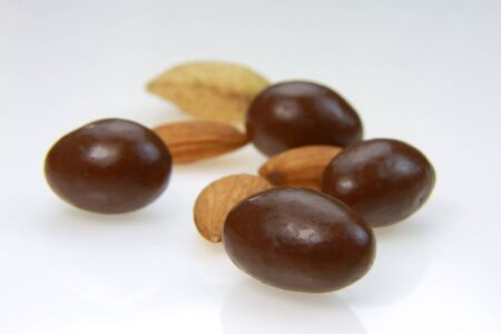 coated: Almonds and almond candy on white background Stock Photo
