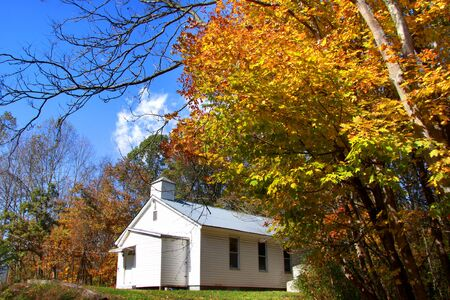 rural town: Historic small church in colorful autumn trees  Stock Photo