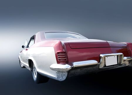 Tail end of white classic car on grey background photo