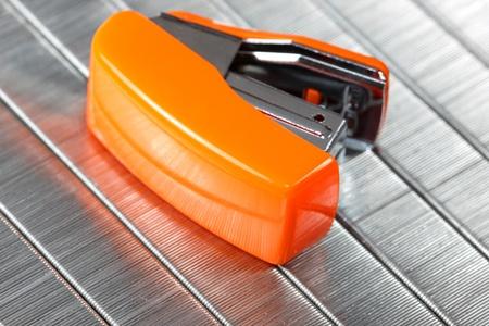grapadora: Pequeña grapadora de naranja contra el fondo de grapas
